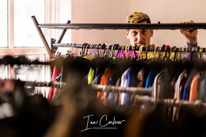 lawson standing behind clothes rack