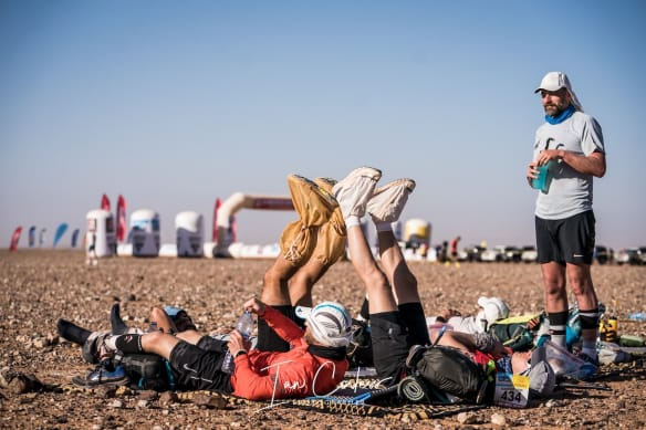 Group of runners resting their legs against each other