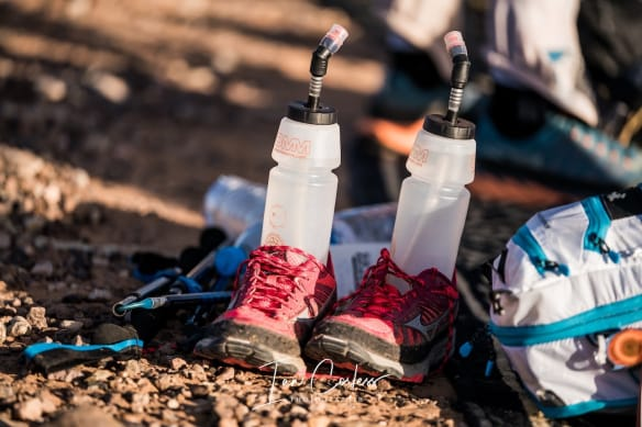 Two water bottles and shoes sitting in the desert sand at then end of a multi-day race